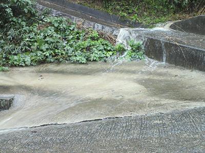 溝が塞がり滝のように流れ落ちる水