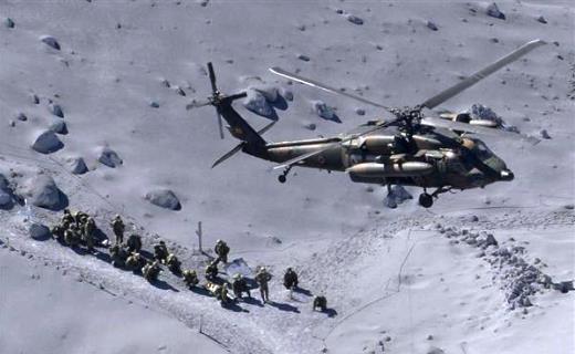 御嶽山山頂付近で救助活動をするUH60JAと自衛隊員ら=9月28日