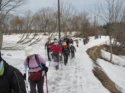 雪残る車道を歩く参加者