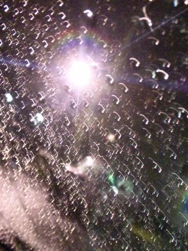 「写真で散歩」フロントガラスの雨しずく 『街灯の周りに虹が!』