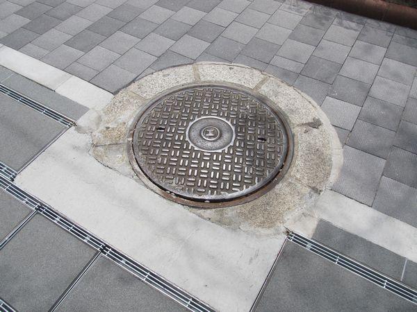 工部省マーク入りのマンホールも排水溝を迂回させて残されている。