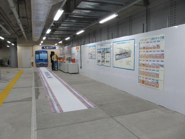 コンコース奥に設置されている地下化工事の情報コーナー。床には将来の線路位置を示すステッカー。