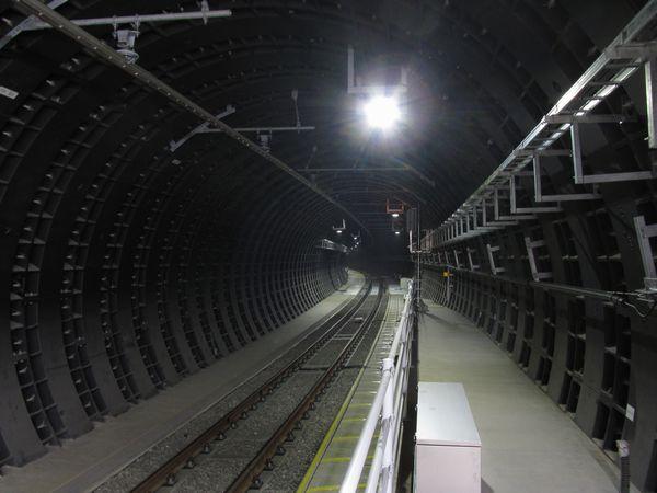 下り線ホーム先端からシールドトンネル内を見る。ダクタイルセグメント特有のゴツゴツした黒い壁面が続く。