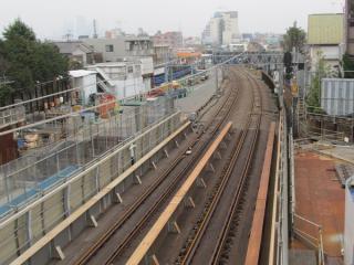 同じ歩道橋から新宿方面の線路を見る。架線の一部は取り外されている。