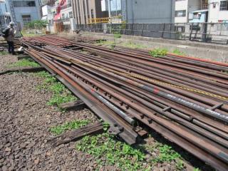 山積みになった交換用レールが列車本数の多さを物語る。