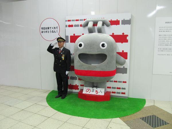 「のるるん」モニュメントの脇で敬礼する毛内定夫・渋谷駅長