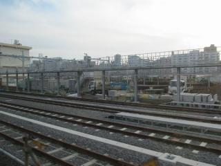 東海道線下り列車から見た金色の留置線群の終端。西側の4本は左の建物に阻まれて途中で終了している。